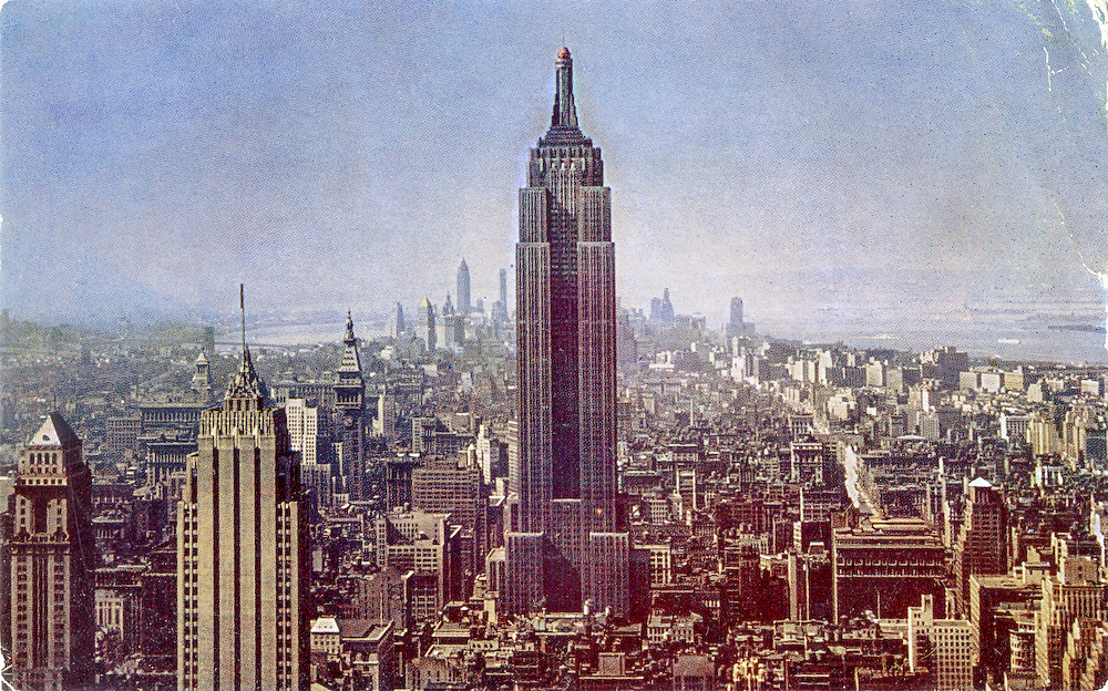 The Empire State Buiding and Midtown and Lower Manhattan as seen from the observation desk of the RCA (formerly General Electric) Building in a vintage postcard, probably from the 1940s. The tower lacks the long television antenna mast that was installed in 1950; and the back of the card says it was shot on Kodachrome -- which was introduced in still photography formats in 1936. So we can say that this image was made sometime between 1936 and 1950.
