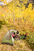 Two women campers sort gear at their tent amid autumn aspens in Utah's Wasatch Mountains