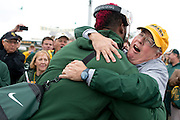 Judge Ken Starr, President and Chancellor of Baylor University, hugs 6'9 defensive lineman Shawn Oakman as he exits the team bus before defeating #9 TCU in Waco, Texas on October 11, 2014. (Cooper Neill for The New York Times)