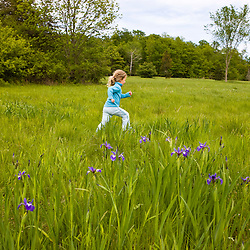 A young girl (age 4) runs through a field at Highland Farm in York, Maine.