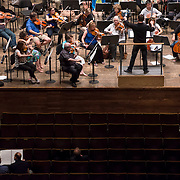 June 3, 2014 - New York, NY : As part of the New York Philharmonic Biennial, the orchestra solicited pieces from little-known composers and will choose three to play. Pictured here, conductor Matthias Pintscher, on podium at top center, leads the New York Philharmonic as it rehearses a composition by composer William Dougherty, who is visible at bottom left, working with mentor composer Derek Bermel on Tuesday. CREDIT: Karsten Moran for The New York Times
