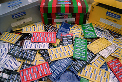 Boxes and pile of different coloured condoms in packets,