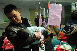 A father holds his child who is receiving an intravenous infusion for respiratory diseases in a hospital in Shijiazhuang City, capital of north China s Hebei Province, Jan. 15, 2013. The number of children suffering from respiratory diseases increased enormously due to prolonged smoggy weather in the past few days, China, January 15, 2013. Photo by Imago / i-Images...UK ONLY