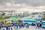 Police after having removed protestors, often by carrying them, are now holding them back between two buses. Another group of police are now ushering trucks carrying tractors and building equipment into Camp Schwab. Henoko, Okinawa, Japan.