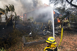 July 6, 2018 - Alpine, San Diego County, U.S. - A firefighter from Heartland Fire in San Diego County tries to keep heat and flames from a burning home from spreading in Alpine Friday afternoon at the West Fire. By afternoon the fire had burned 400 acres, destroyed multiple homes, and was 0% contained. (Credit Image: © Stuart Palley via ZUMA Wire)