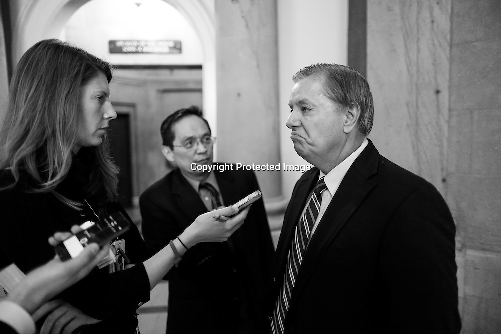 U.S. Senator Lindsey Graham (R-SC) (R) talks to reporters on his way to a Senate Republican caucus at the U.S. Capitol in Washington, October 12, 2013.