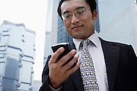 China Hong Kong business man text messaging standing in business district low angle view