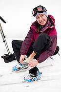 A female skier checks her feet for blisters while touring to Peter Estin hut in a snow storm in Colorado.  Telemark or AT skis with climbing skins are used to climb up steep snow slopes when doing backcountry skiing.