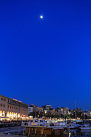 The moon shines over the Barcelona Port in Barcelona, Spain