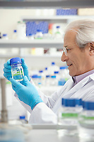 Scientist looking at specimen bottle in laboratory