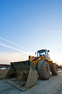 A wheeled loader with a large bucket rests temporarily at a large new housing project being built near Joliet, IL.