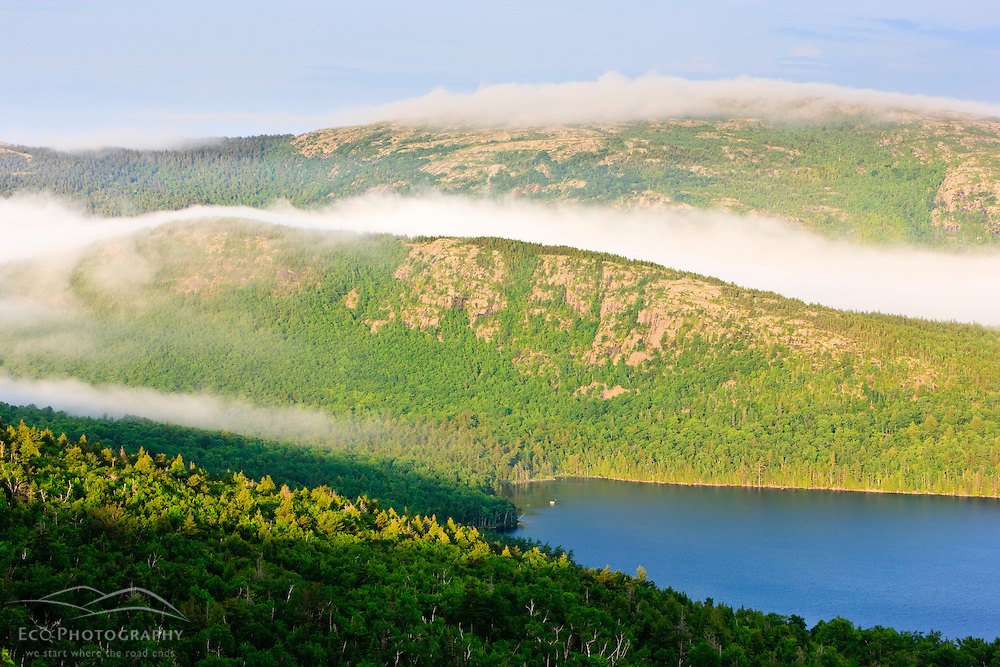 Morning fog hugs the summit of Sargent Mountain above Eagle Lake in Maine's Acadia National Park.  As seen from Cadillac Mountain.
