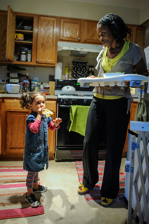 photo by Matt Roth..Takoma Village Cohousing resident Georgette Small, a school councilor, preps her daughter JoJo Small's baby sitter Sidney Smith, 17, before leaving for a school function Thursday, September 20, 2012. ..Rather than pay a property management company, the twelve-year-old Washington, D.C. condominium complex is governed by its' residents. The Cohousing movement started in the Netherlands in the 60's and is gaining momentum in the states.