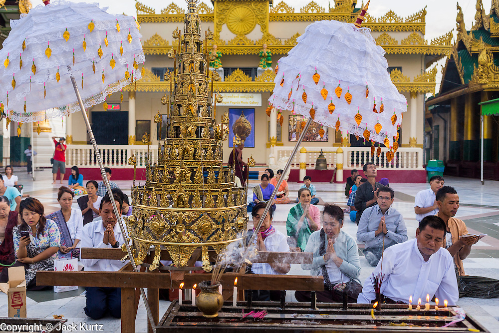 15 JUNE 2013 - YANGON, MYANMAR: People pray on a plaza on the northeast side of Shwedagon Pagoda. Shwedagon Pagoda is officially known as Shwedagon Zedi Daw and is also called the Great Dagon Pagoda or the Golden Pagoda. It is a 99 meter (325 ft) tall pagoda and stupa located in Yangon, Burma. The pagoda lies to the west of on Singuttara Hill, and dominates the skyline of the city. It is the most sacred Buddhist pagoda in Myanmar and contains relics of the past four Buddhas enshrined: the staff of Kakusandha, the water filter of Koṇāgamana, a piece of the robe of Kassapa and eight strands of hair from Gautama, the historical Buddha. Burmese believe the pagoda was established as early ca 540BC, but archaeological suggests it was built between the 6th and 10th centuries. The pagoda has been renovated numerous times through the centuries. Millions of Burmese and tens of thousands of tourists visit the pagoda every year, which is the most visited site in Yangon. PHOTO BY JACK KURTZ