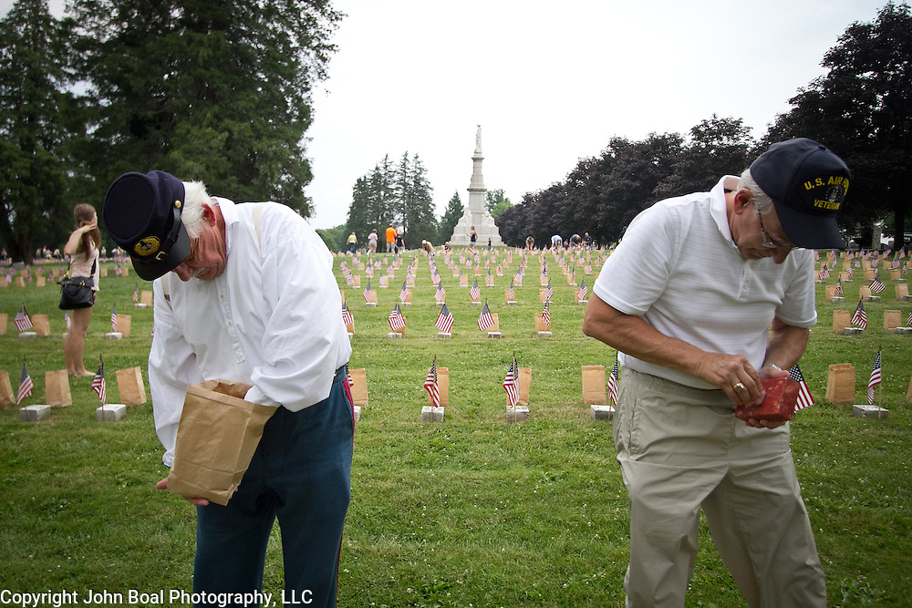 """Volunteers, John Reynolds, left and Bill Presutti, prepare luminaria at the Soldiers National Cemetery, during the Sesquicentennial Anniversary of the Battle of Gettysburg, Pennsylvania on Sunday, June 30, 2013.   Following """"A New Birth of Freedom"""" program at Meade's Headquarters, a procession by candlelight was led to the cemetery. John Boal photography"""