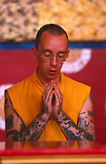 A follower of Tibetan-Buddhism engages in Puja, or prayer, at the Kagyu Samye Ling Monastery and Tibetan Centre in Eskdalemuir, Scotland. This young western man wears traditional Tibetan monk's clothes, is adorned with tattoos and has his head shaven. He is a western visitor, many of whom have had a troubled youth and are sometimes escaping a criminal past, who arrive in the Scottish wilderness for isolated Retreat periods, for short-term spiritual relaxation or to follow Tibetan teaching methods for discovering inner-peace, through prayer and meditation. This Tibetan Buddhist complex associated with the Kagyu school celebrates its 40th anniversary in 2007.