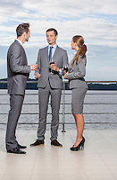 Full length of young businesspeople holding wineglasses while communicating on terrace
