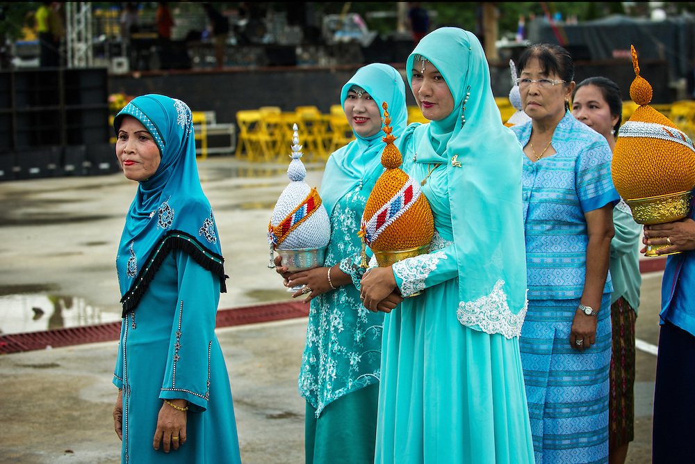 Thai Muslim woman, dressed in blue, the Queen's color, cary Pan-Pum's, the symbol of Thai royalty, to place by the Queen's photo as Rural Thailand celebrates HM Queen Sirikit's birthday in Nakhon Nayok, Thailand.