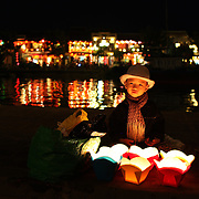 A young vietnamese boy helps his mother sell floating candles to tourist by the side of the Thu Bon River, Hoi An, Vietnam. Hoi An is an ancient town and an exceptionally well-preserved example of a South-East Asian trading port dating from the 15th century. Hoi An is now a major tourist attraction because of its history. Hoi An, Vietnam. 5th March 2012. Photo Tim Clayton