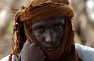 "Abu Gudam, Chad: A young Arab nomad in Eastern Chad. Camel and cow-herding nomads here say that the government and its allied militias are targetting them in a divide-and-conquer strategy aimed a subduing a rebellion. While Chadian nomads have participated in the atrocities in neighboring Darfur, Arab nomads here feel the government is unfairly branding all of them ""janjaweed.""  Chad is home to over 200 different ethnic and linguistic groups. Arabic and French are the official languages. Islam and Christianity are the most widely practiced religions. Chad is one of the poorest and most corrupt countries in the world; most inhabitants live in poverty as subsistence herders and farmers. Since 2003, crude oil has become the country's primary source of export earnings, superseding the traditional cotton industry. (PHOTO: MIGUEL JUAREZ LUGO)."