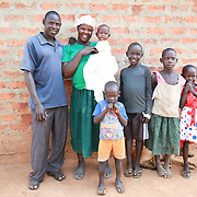 CAPTION: Catherine Anaso together with her husband and their children: a family portrait. LOCATION: Apapai Parish, Otuboi Sub-county, Kalaki County, Kaberamaido District, Uganda. INDIVIDUAL(S) PHOTOGRAPHED: From left to right: David Alele, Catherine Anaso, Silas Oper, Daniel Owange, Innocent Jacob Okot, Cecilia Acwichi and Nancy Acen.