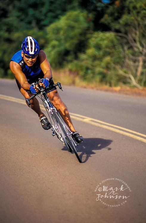 Hawaii, Kauai, man speeding downhill on his road bicycle