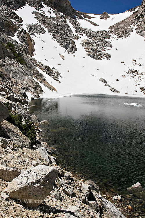Glacial tarns and lakes are common in the High Sierras and are formed during glacial and periglacial conditions.  Ice has tremendous power when under pressure and carves the underlying rock as glaciers move towards lower elevations.  Glacial lakes and alpine tarns can be formed at the upper edge of a glacier