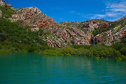 Mangroves line the shoreline under sandstone cliffs in Talbot Bay, part of the Buccaneer Archipelago on the Kimberley coast.