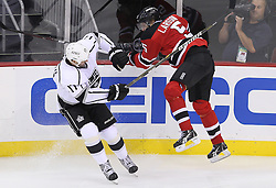 Oct 13; Newark, NJ, USA; Los Angeles Kings left wing Ethan Moreau (17) hits New Jersey Devils defenseman Adam Larsson (5) during the third period at the Prudential Center. The New Jersey Devils defeated the Los Angeles Kings 2-1 in an OT shootout.