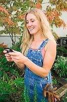 A late 20's woman text messaging in an outdoor garden / nursery setting