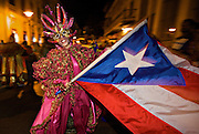 A costumed reveler called vejigante dances in the street with a Puerto Rican flag during the Carnaval de Ponce February 21, 2009 in Ponce, Puerto Rico. Vejigantes are a folkloric character representing the devil.