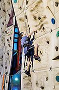 Boy scaling an indoor rock climbing wall.