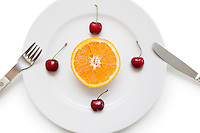Sliced orange and cherries arranged in a plate with fork and knife over white background