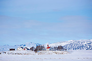 Quaint church Braedratungukirkja with typical traditional red roof in snowy landscape in Iceland