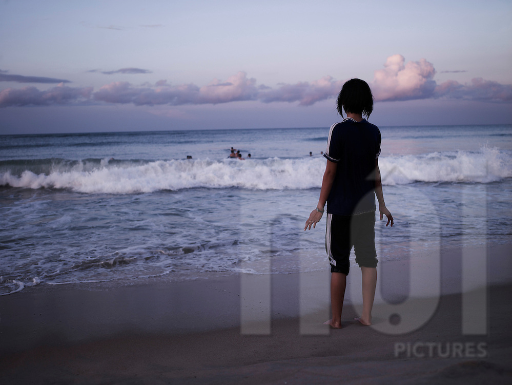 A vietnamese girl stands on the beach and looks over a group of people swimming. Danang, Vietnam, Asia.