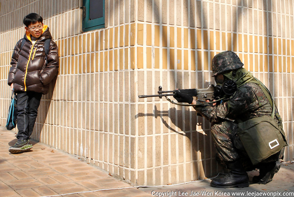 A primary school student looks at a soldier attending an anti-terrorism drill held in preparation for the Seoul Nuclear Security Summit, at a park in Seoul March 9, 2012. /Lee Jae-Won