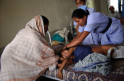 KATHMANDU, NEPAL, APRIL 14, 2004: Nepali nurses  and his mother look after Sunil Sharma, 9 years old, in a hospital in Nepalganj, Nepal who was injured in an explosion 10 days earlier by Maoist insurgents fighting government forces April 14, 2004.  Over two thousand children have been killed in the fighting which began in 1996.  (Ami Vitale/Getty Images)