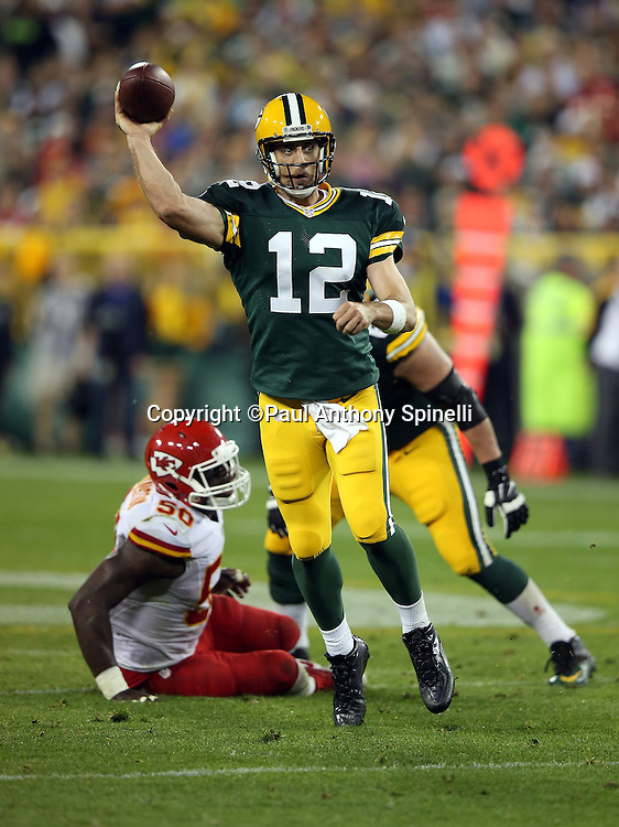 Green Bay Packers quarterback Aaron Rodgers (12) scrambles away from pressure by Kansas City Chiefs outside linebacker Justin Houston (50) as he throws a second quarter pass during the 2015 NFL week 3 regular season football game against the Kansas City Chiefs on Monday, Sept. 28, 2015 in Green Bay, Wis. The Packers won the game 38-28. (©Paul Anthony Spinelli)