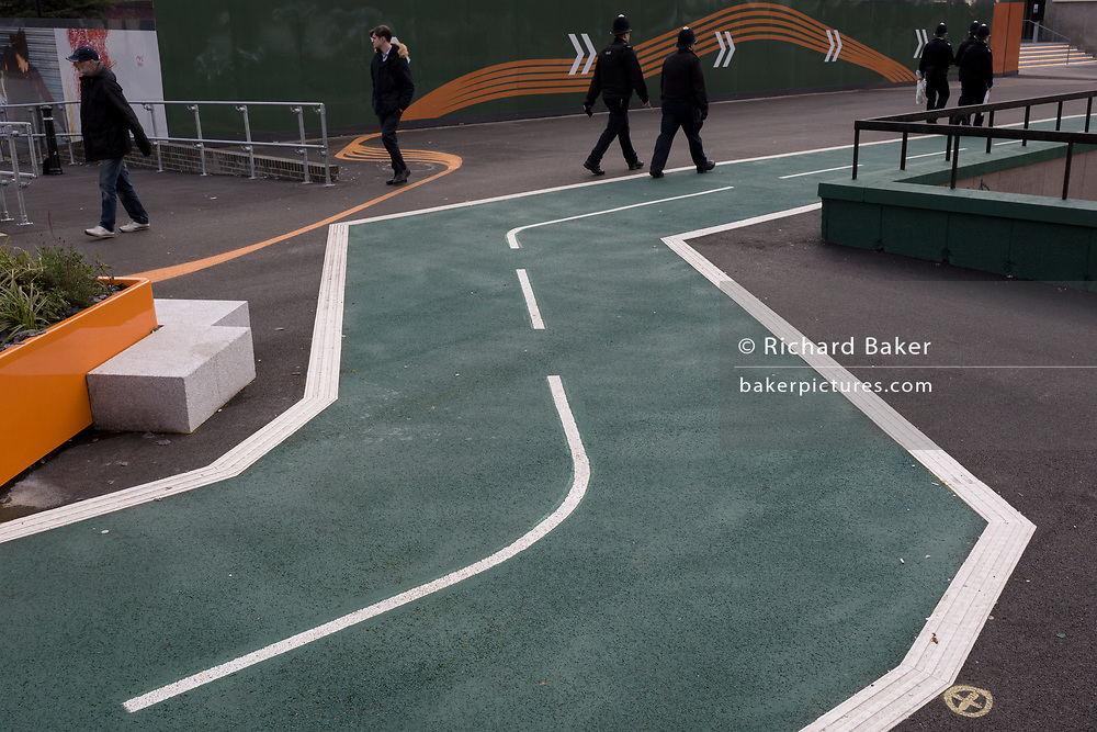 Police officers walk past a new cycling path, a regenerated landscape created outside Croydon College and Fairfield Hall, on 20th January 2020, in Croydon, London, England.