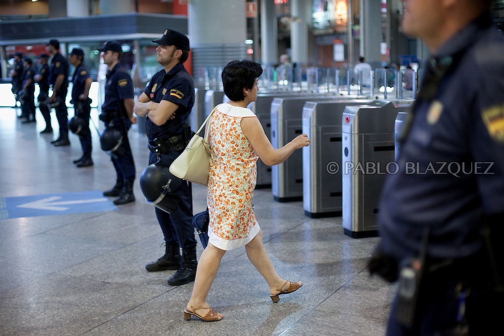 A train user walks through riot police guarding the gates access to trains during a rail workers demonstration againts government's privatisation plans in Puerta de Atocha rail staition in Madrid on August 3, 2012. Hundreds of trains have been cancelled in Spain during the 24 hours strike by rail workers protesting against privatisation plans.