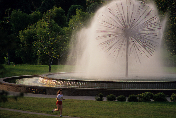 Stock photo of a woman jogging by the Gus Wortham fountain in the early evening