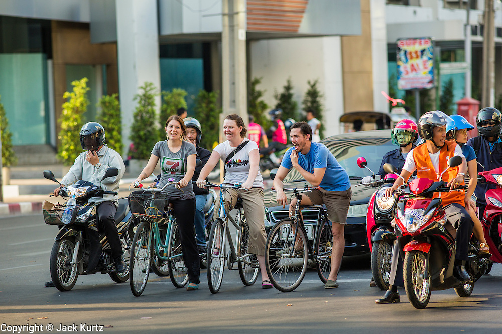 01 APRIL 2013 - BANGKOK, THAILAND:    Tim and Amy Hupe and Molly Evans navigate Bangkok's chaotic streets on bikes. PHOTO BY JACK KURTZ