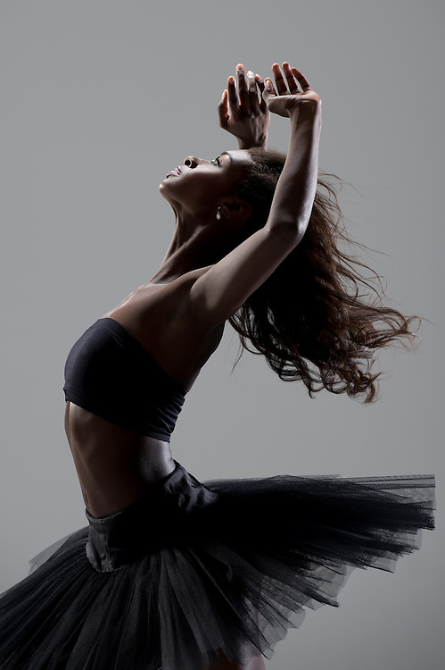 Classical ballet ballerina, Ashley Murphy, bending back with a black tutu on. Taken in the photo studio on a grey background. Photograph taken in New York City by photographer Rachel Neville.