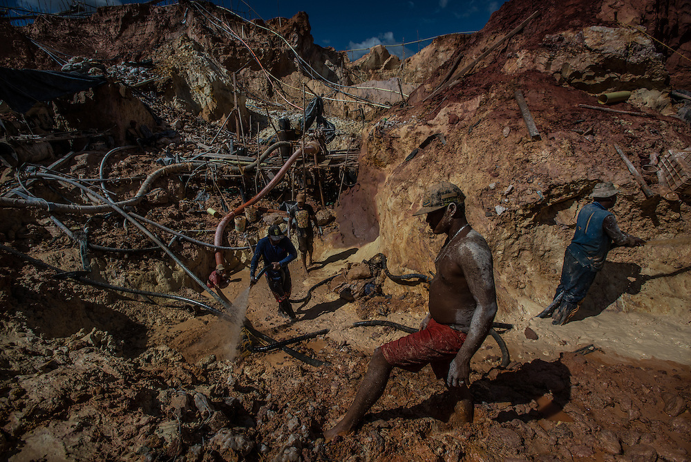 """LAS CLARITAS, VENEZUELA - JULY 20, 2016:  Carlos Raphael, 50, (right) and his crew illegally mine for gold at the """"Cuatro Muertos"""" (""""Four Dead"""") mine, named so because four miners have died here since the mine was dug.  Raphael has contracted malaria ten times, and said everyone in his crew has also had it multiple times.  Thousands of Venezuelans are flocking to illegal gold mines, like this one, in hopes of surviving the current economic crisis by earning in gold instead of the national currency, whose value steadily falls due to the world's highest inflation.  From this remote part of the jungle the migrant miners have become the vectors of a new epidemic of malaria, because the hot, swampy conditions of the mines make for an ideal breeding ground for mosquitos. Miners spread the disease as they return home with earnings or pay visits to family members. The economic crisis has also left the government without the financial resources to control the disease - they are unable to fumigate homes, provide medicines to everyone that is sick, or even to test all patients with symptoms of malaria in many places. PHOTO: Meridith Kohut"""