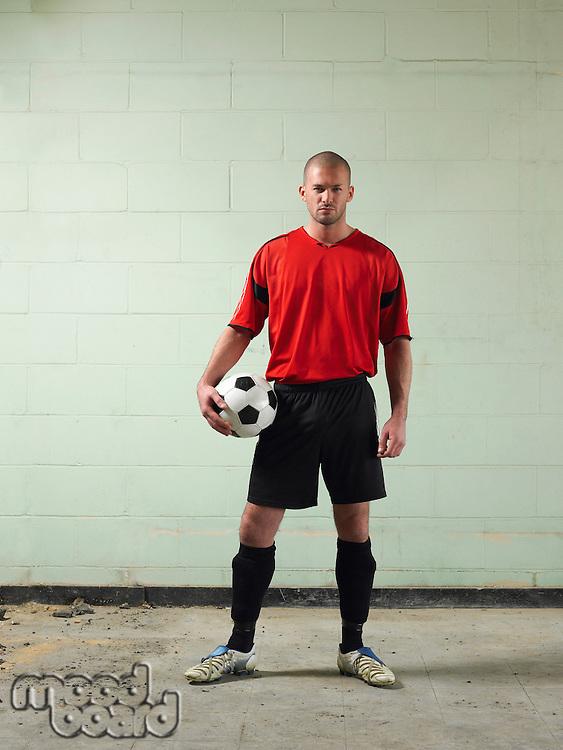 Soccer player holding ball portrait