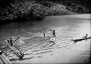 10..Tagbanua children paddle bamboo rafts in cove, Coron Island, Philippines.