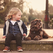 Cute toddler and pet dog in Battersea Park, London