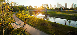 Jogger enjoying a morning run on the Hike and Bike Trail at Buffalo Bayou as the sun rises with the Houston, Texas skyline in the background.