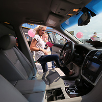 Lauren Ward and her daughter, Chaislyn, 14 months, take a closer look at the Cadillac SRX Ward won by submitting an essay to the NAPA AutoCare Centers of Northeast Mississippi that explained why why their mother deserved a reliable car.