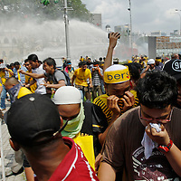 Malaysian protestors run from water cannon during a BERSIH  rally in Kuala Lumpur, Malaysia 28 April 2012. BERSIH protest is a protest organised by the opposition party demanding for a clean and fair election. Malaysian  general election is not due until 2013, but there has been speculation that Prime Minister Najib may call an earlier vote.